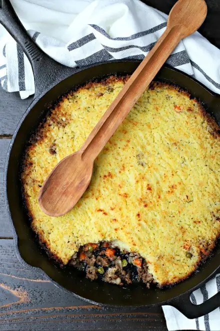 overhead shot of a large cast iron skillet with cooked shepherds pie topped with a long wooden spoon and on top of a black and white linen on a table