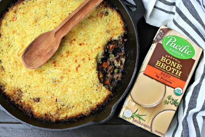 cooked skillet shepherds pie with a wooden spoon on top next to a carton of beef bone broth