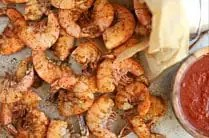 close up overhead shot of cooked old bay shrimp topped with extra old bay seasoning with wood bowl filled with cocktail sauce