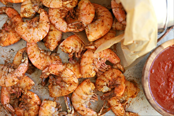 close up overhead shot of cooked old bay shrimp boil topped with extra old bay seasoning with wood bowl filled with cocktail sauce
