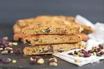 close up of three gluten free biscotti stacked on top of eachother with loose pistachios and cranberries on the table next to a beige frayed linen