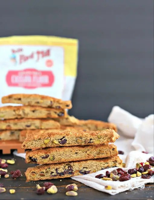 stacks of gluten free biscotti with scattered pistachios and cranberries in front of a bag of Bob's Red Mill Cassava flour