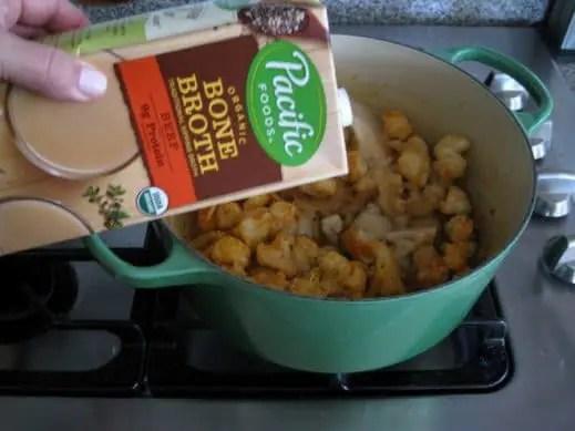 adding Beef Bone Broth to a pot of ingredients to make Garlic Soup