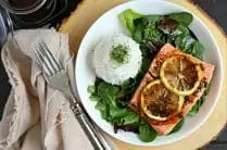 white plate with bed of mixed greens, cooked salmon topped with sliced lemon and ball of white rice topped with spinach seasoning. balsamic dressing drizzled on top of salmon and salad