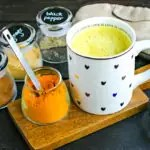 mug of golden milk with jars of spices