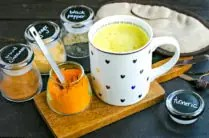 mug of turmeric milk with jars of spices and a sleeping mask