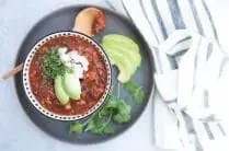 close up of turkey black bean chili in a bowl topped with avocado, white onion and cilantro