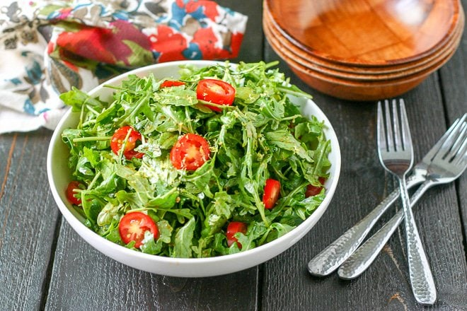 bowl of arugula salad with cherry tomatoes and wood bowls for serving