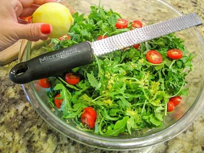 zesting a lemon into arugula salad