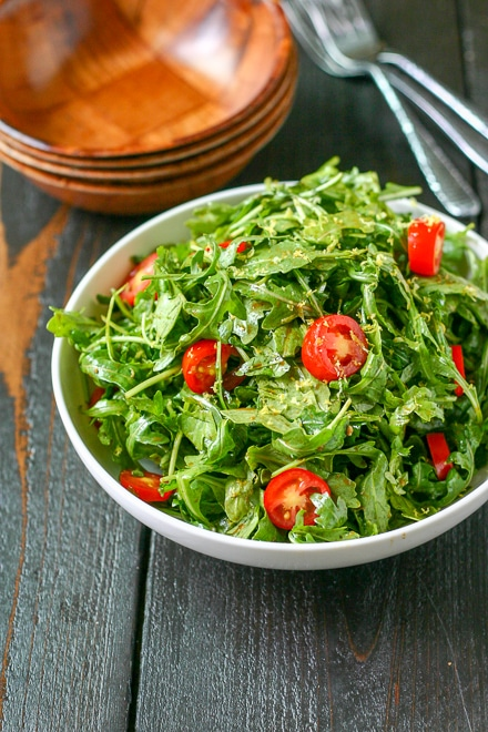 arugula salad with balsamic in a white bowl