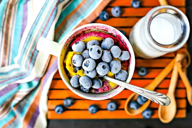 overhead shot of frozen blueberries on a blueberry mug cake