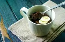 single serving chocolate mug cake topped with sliced bananas with a spoon