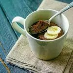 beige mug with microwave chocolate mug cake recipe topped with sliced banana