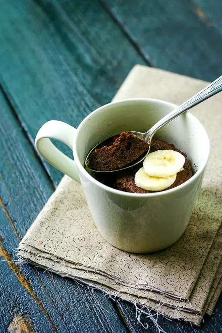 chocolate mug cake in a beige mug with a spoon and sliced banana