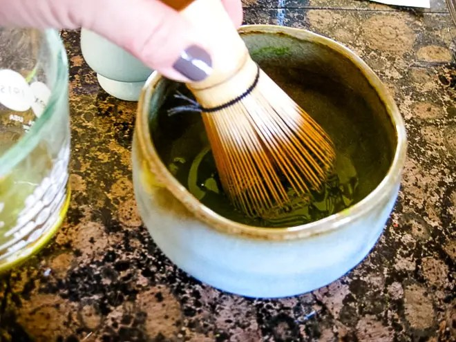 using a bamboo whisk to make a smooth matcha paste in a bowl