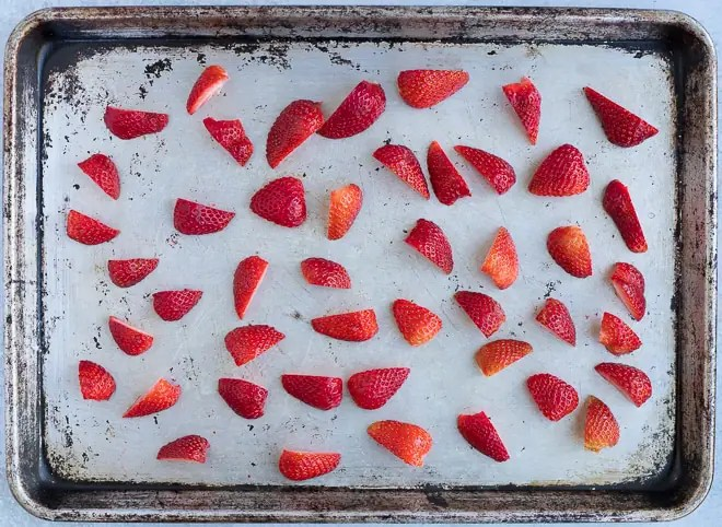 baking sheet of halved strawberries for roasting