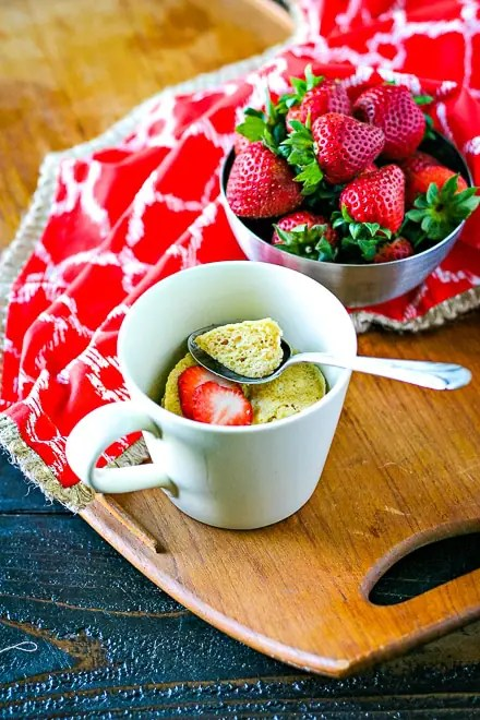 vanilla mug cake in a small mug with a silver spoon and bowl of strawberries