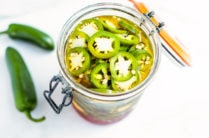 a glass jar stuffed with homemade pickled jalapenos