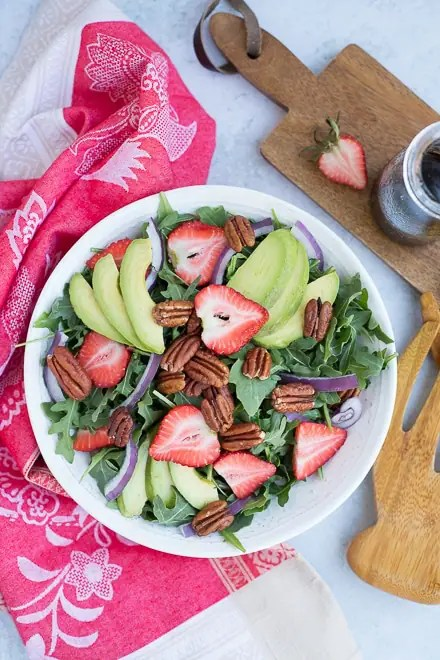 overhead view of strawberry salad with avocado, pecans and red onion on a bed of arugula