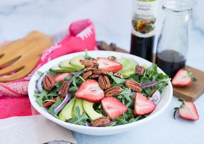 strawberry salad in a white serving bowl with balsamic dressing in a glass jar