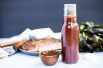 glass bottle of A1 steak sauce in front of cooked steak