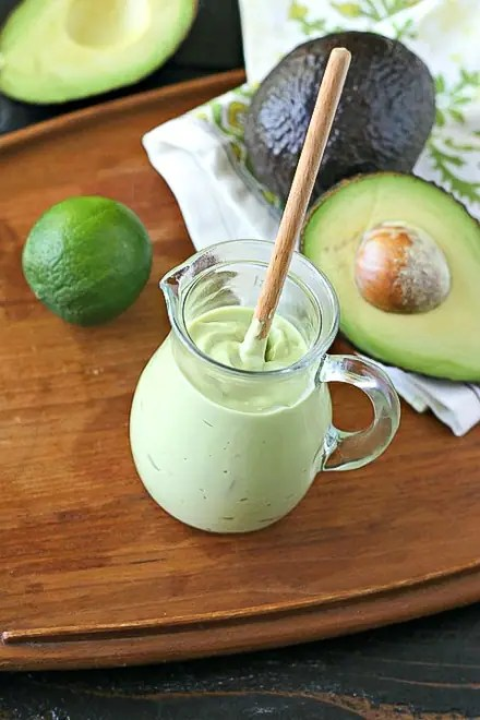 vegan avocado crema in glass jar on a wood tray with cut avocado and lime