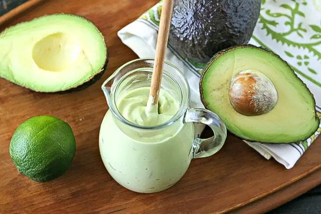 Avocado Crema recipe in a glass jar with cut avocadoes and lime