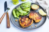 plate of salmon cakes with lemon, lettuce, and dipping sauce