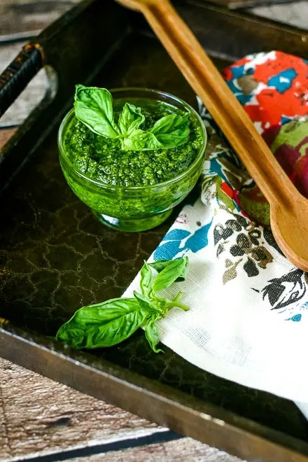 vegan pesto in small dish with fresh basil on a serving tray