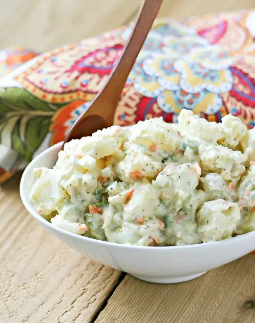 close up of classic potato salad in a white serving bowl with a brown wood spoon