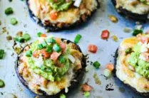 stuffed portobello mushrooms topped with guacamole and salsa on a baking sheet