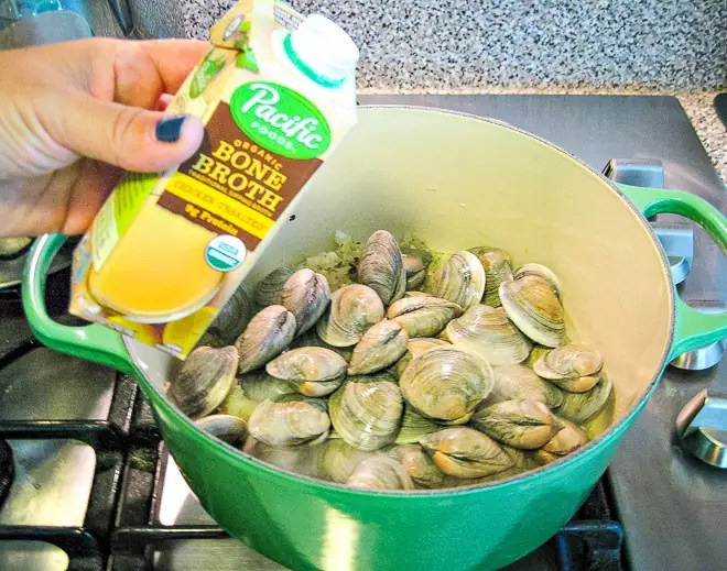 pouring broth into pot with littleneck clams