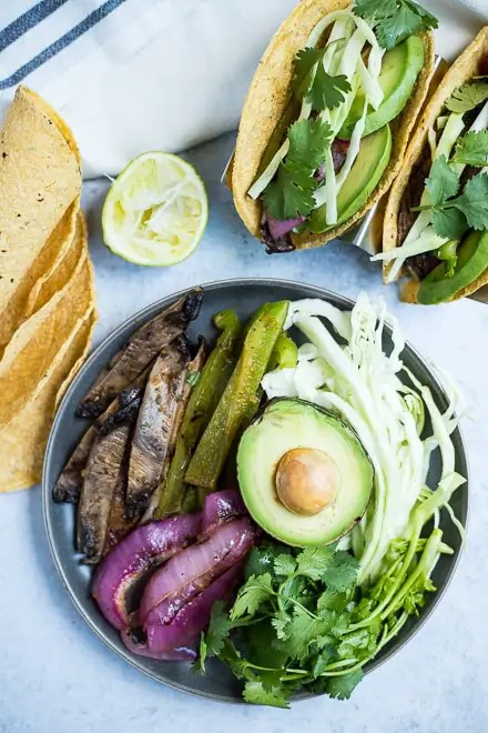 overhead photo of cooked vegan tacos on a platter with half of an avocado