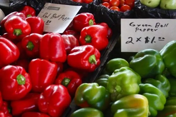 red and green bell peppers for sale in a grocery store bin