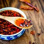 bowl of homemade chili oil with wood spoon and whole chilies