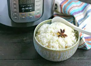 bowl of cooked instant pot rice with star anise on top in front of instant pot