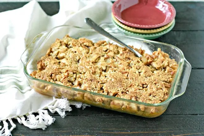 apple cranberry crisp in a glass baking dish with serving spoon and colorful plates