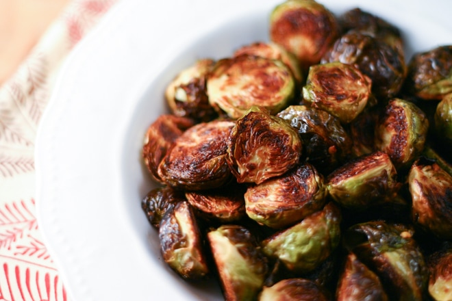 white bowl filled with crispy roasted brussels sprouts and patterned linen