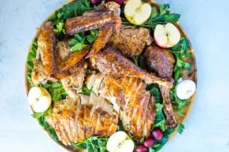 wood circle platter with roast turkey, sliced apples, greens and grapes ready to be served