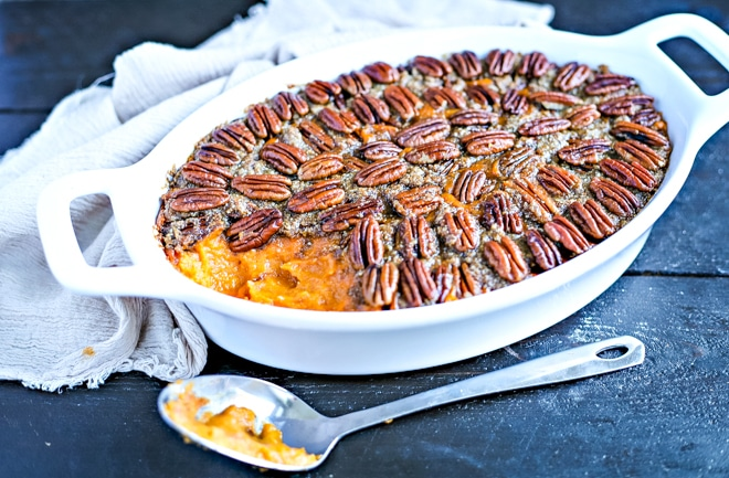 healthy sweet potato casserole topped with pecans in white baking dish