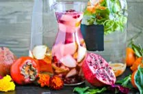 glass pitchers filled with fruit infused water with cut fruit around the bottles