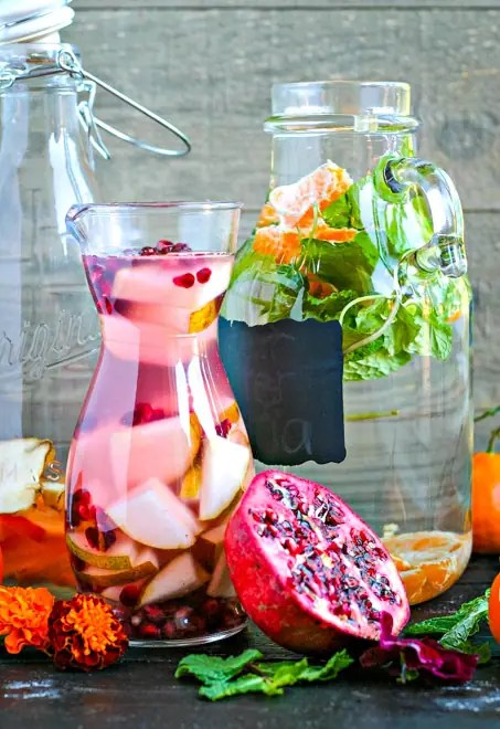 large glass pitchers filled with fruit and herb water
