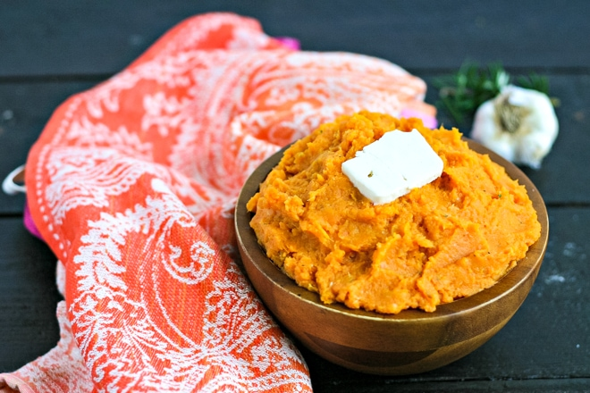 wood bowl of mashed sweet potatoes topped with butter next to an orange linen