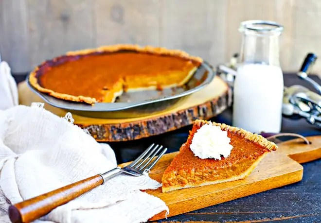 slice of paleo pumpkin pie with whipped cream on top in front of glass of milk