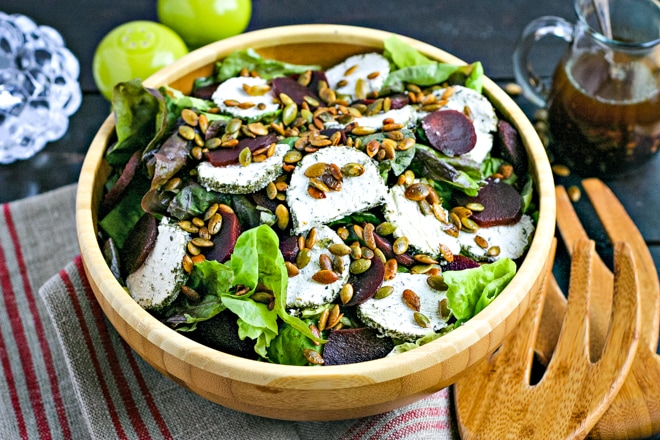 salad bowl with festive thanksgiving salad topped with crispy pumpkin seeds