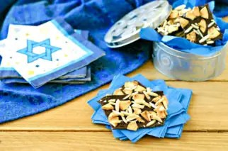 hanukkah candy on blue napkins with a silver tin filled with more candy