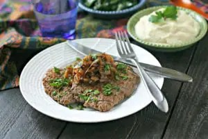white plate with cooked cube steak topped with chopped parsley