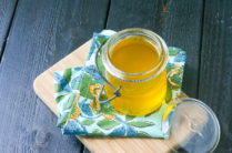 jar of ghee with a blue and yellow linen on a wood cutting board