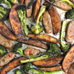 close up of cooked sausage, potatoes and broccoli on a sheet pan