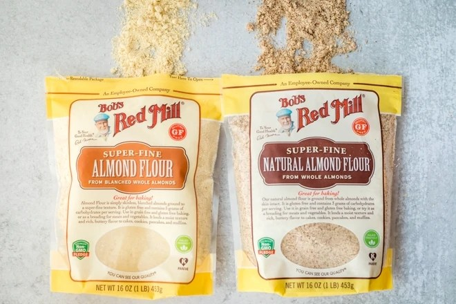 a bag of bob's red mill almond flour next to a bag of bob's red mill natural almond flour showing the difference between the types of flour